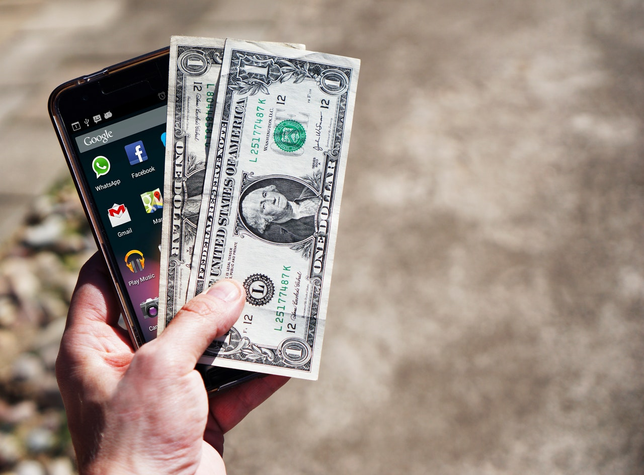 Smartphone and money in hand
