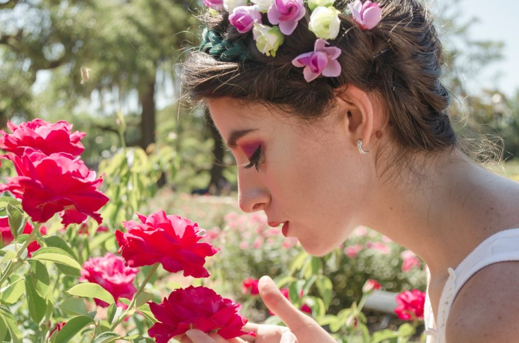 woman-in-floral-headdress-sniffing-on-red-flowers